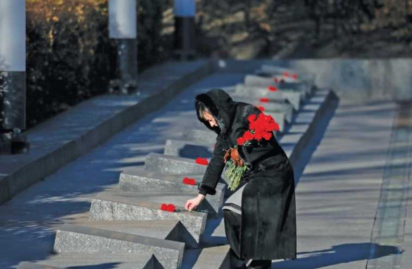 A WOMAN lays flowers during a wreath laying ceremony at the Unknown Soldier's Tomb in Kiev (photo credit: REUTERS)