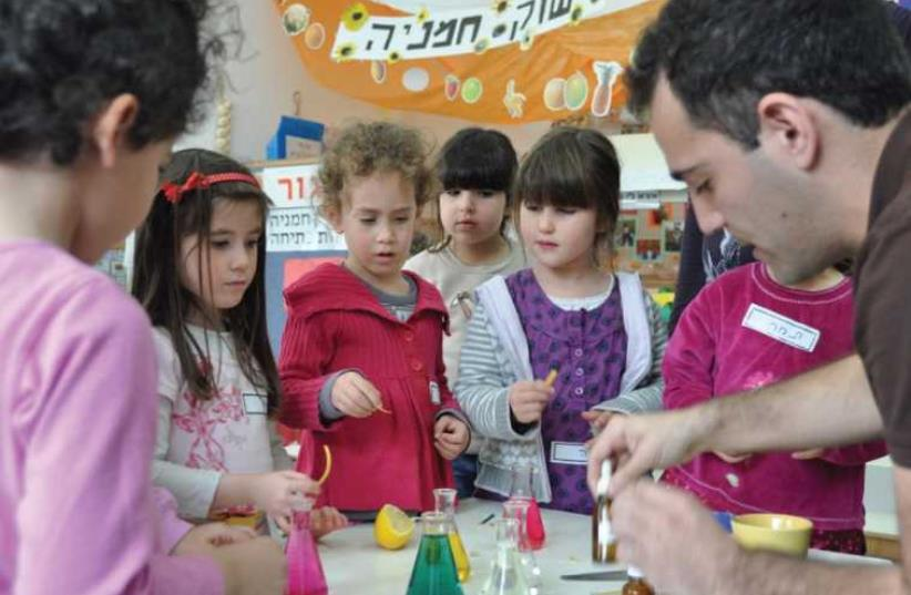 Dr. Assaf Marom teaches kindergarten students about acids and alkaline substances at a Science Day event (photo credit: SCIENCE, TECHNOLOGY AND SPACE MINISTRY)