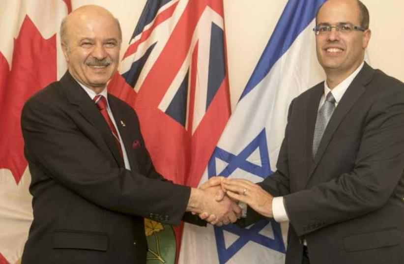 Ontario's Minister of Research and Innovation Reza Moridi, Left, shakes hands with Chief Scientist Avi Hasson. (photo credit: YOSSI ALONI)