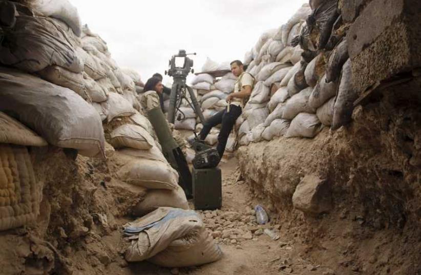 Rebel fighters of Al-Sultan Murad brigade rest amid sandbags near Aleppo's international airport in May (photo credit: REUTERS)