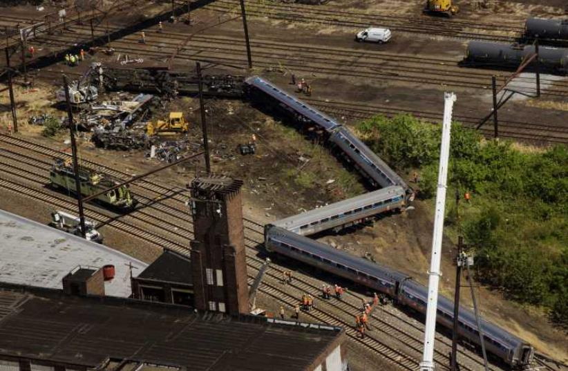 Emergency workers and Amtrak personnel inspect a derailed Amtrak train in Philadelphia, Pennsylvania  (photo credit: REUTERS)