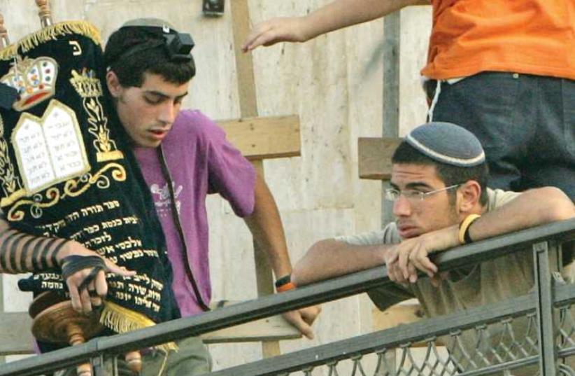 A man holding Torah scroll (photo credit: REUTERS)