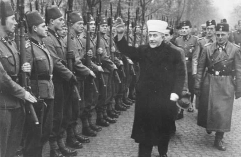 Nakba instigator Husseini giving the Heil Hitler salute to Bosnian Muslim volunteers to the notorious Waffen SS (the Hanzar SS Division) in November, 1943 [Jerusalem Post Archives]    (photo credit: JERUSALEM POST ARCHIVE)