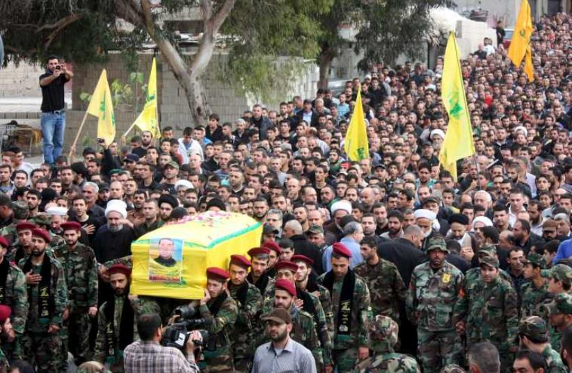 Hezbollah members in Lebanon take part in a funeral procession for their comrade Akram Sadek Hourani, who was killed in the recent battles in Syria's Qalamoun region. (photo credit: REUTERS)