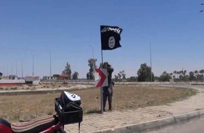 ISIS flag flying in Ramadi Iraq (photo credit: AAMAQ NEWS VIA YOUTUBE / AFP)