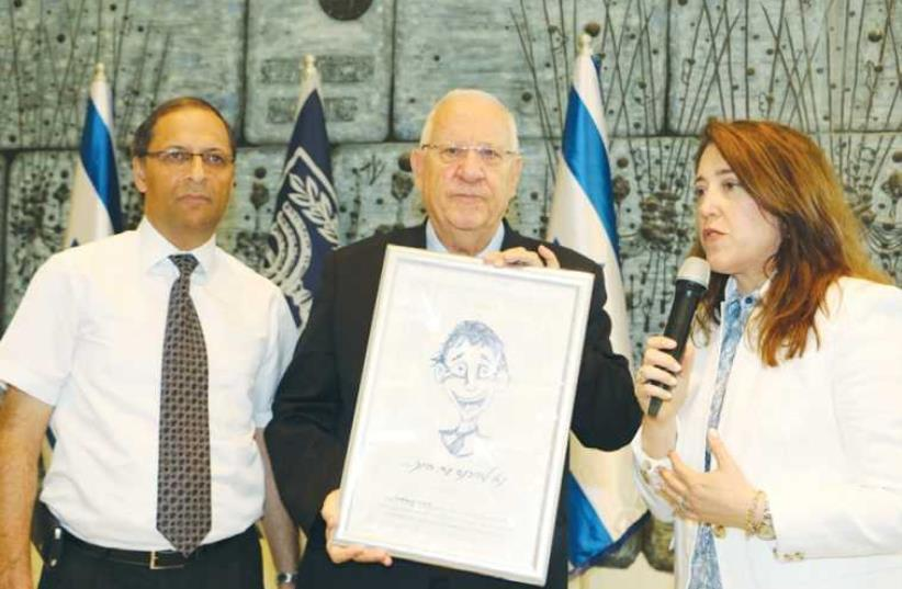 AMNON ELDAR and Debbie Isaac of Amit present President Reuven Rivlin with the plaque at the President's Residence in Jerusalem (photo credit: COURTESY AMIT)