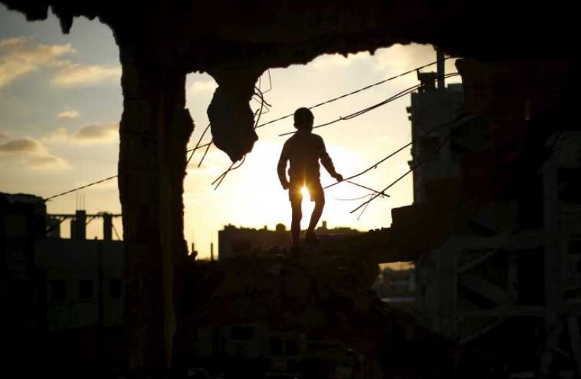 A Palestinian boy plays at a house that witnesses said was destroyed during Operation Protective Edge in the east of Gaza City (photo credit: REUTERS)