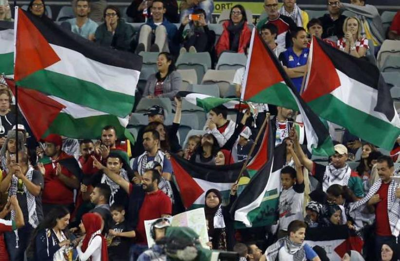 Fans of the Palestinian national team wave flags during their Asian Cup Group D soccer match against Iraq (photo credit: REUTERS)