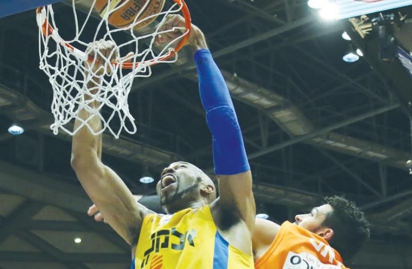 Maccabi Tel Aviv center Alex Tyus dunks two of his 16 points in Sunday's 90-73 win over Ironi Ness Ziona (photo credit: ADI AVISHAI)