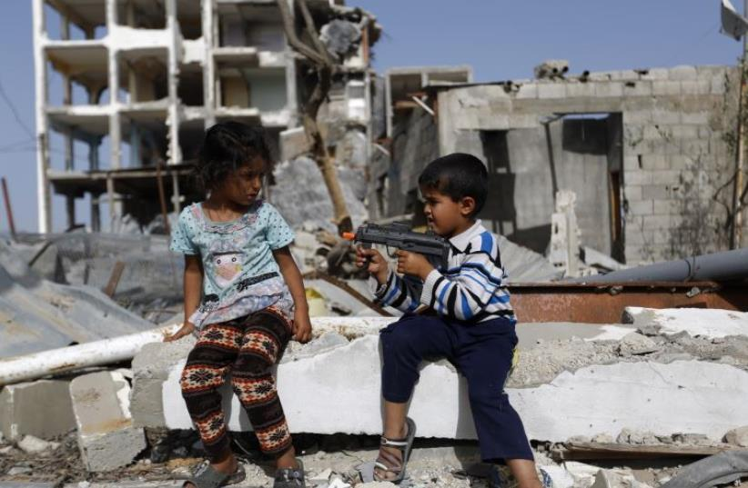 Palestinian children play with a toy gun in front of homes ruined during Israel's bombardment in 2014 (photo credit: MOHAMMED ABED / AFP)