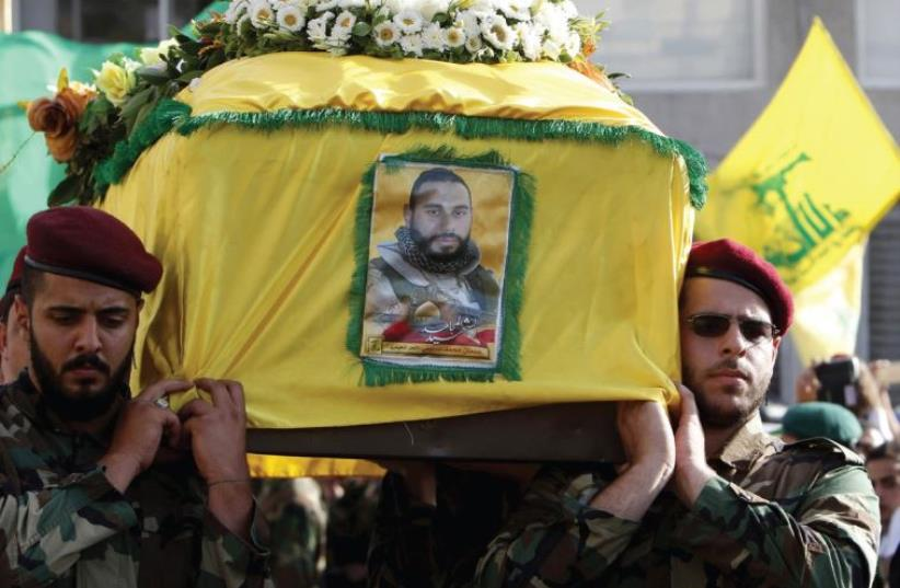 HEZBOLLAH MEMBERS carry the coffin of Adnan Siblini on Tuesday, who was killed in the Qalamoun region, during his funeral in al-Ghaziyeh. (photo credit: REUTERS)