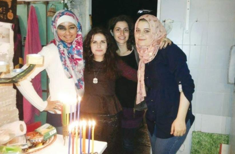 (From left to right) Rana , Ruth, her sister and Sajida take a group photo after lighting Hanukka candles last year. (photo credit: COURTESY RUTH VASILEVA)
