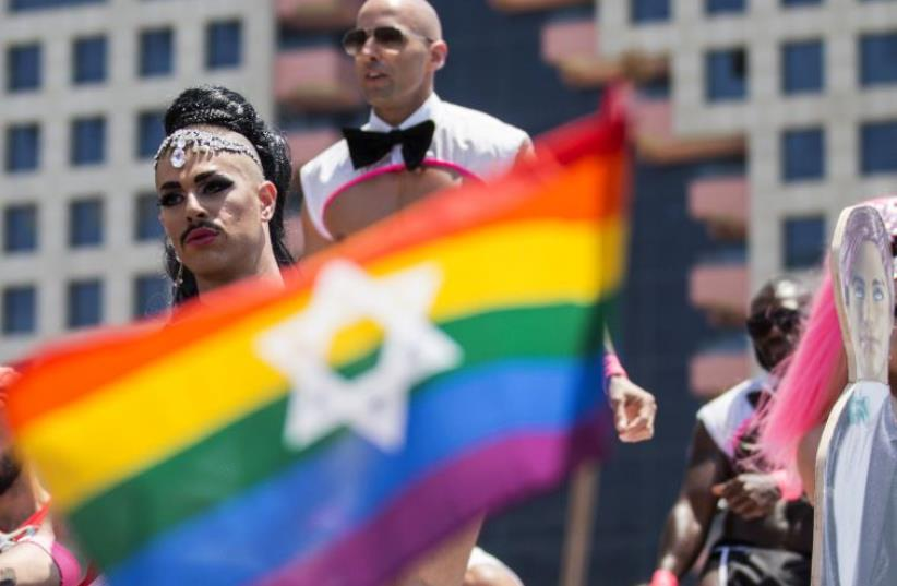 Israeli drag queens and go-go dancers dance on a truck during the annual gay pride parade in the Israeli coastal city of Tel Aviv on June 13, 2014.  (photo credit: JACK GUEZ / AFP)