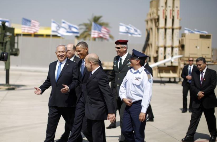 US President Barack Obama walks with Prime Minister Benjamin Netanyahu as he views an Iron Dome Defense Battery at Ben-Gurion International Airport, March 20, 2013. (photo credit: REUTERS)