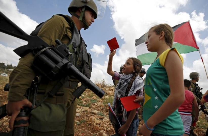 Palestinian girls hold red cards in front of an IDF soldier during a rally near Ramallah in support of a Palestinian move to have Israel suspended from FIFA (photo credit: REUTERS)
