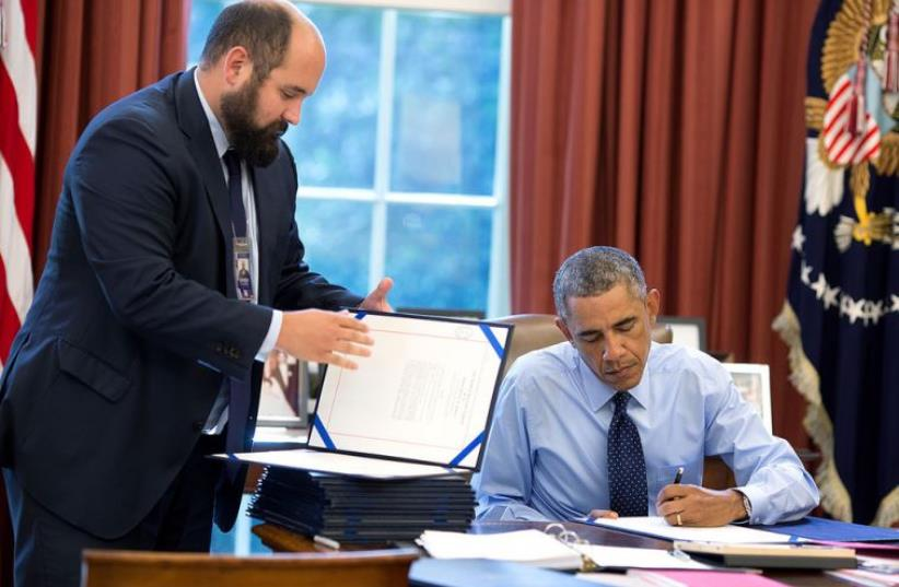 President Barack Obama, assisted by Deputy Staff Secretary Ted Chiodo, signs bills in the Oval Office (photo credit: OFFICIAL WHITE HOUSE PHOTO / PETE SOUZA)