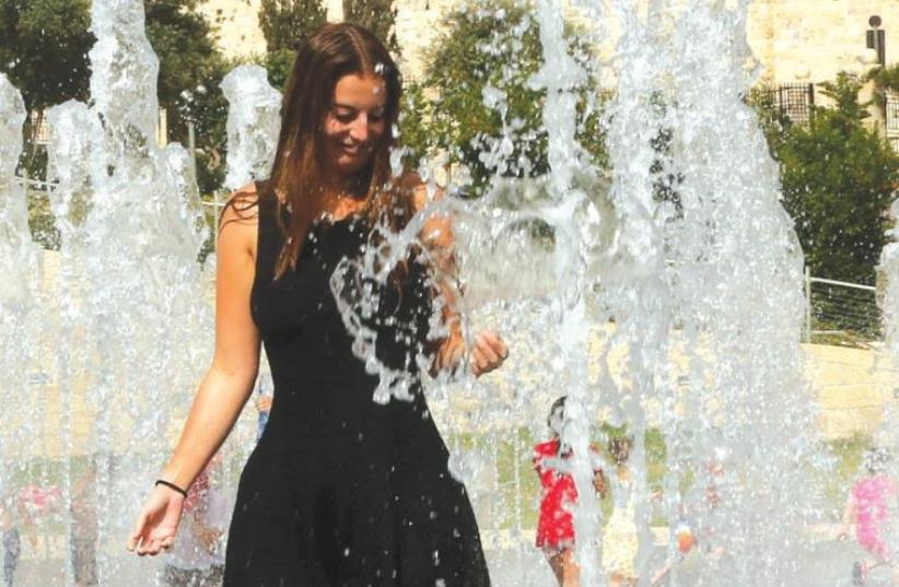 A woman plays in a water fountain in Jerusalem (photo credit: ILLUSTRATIVE: MARC ISRAEL SELLEM)