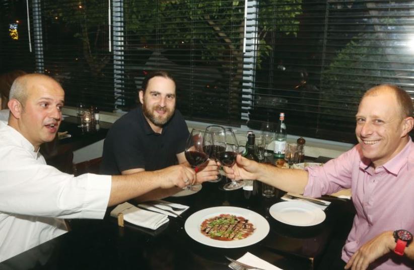Designer Yaron Loubaton (right) raises his glass with chef Moti Ahana (left) and interviewer Asaf Finkelstein. (photo credit: ILLUSTRATIVE: MARC ISRAEL SELLEM)