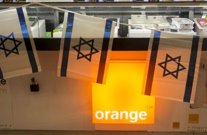 Israeli flags hang over the counter for the Orange mobile company at a mall in Tel Aviv (photo credit: REUTERS)