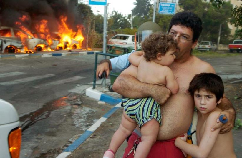 An Israeli man stands with his children at the scene of a rocket attack in Haifa, August 13, 2006 (photo credit: REUTERS)