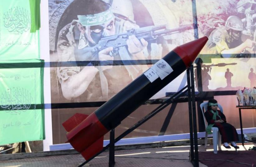 A Palestinian girl sits next to a mock rocket during a rally honoring families of Palestinians who were killed by Israeli forces (photo credit: REUTERS)