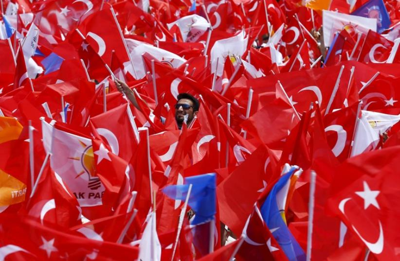 Supporters of the ruling AK Party wave Turkish national and party flags at an election rally for Turkey's June 7 parliamentary election, in Antalya, Turkey, June 6, 2015 (photo credit: REUTERS)