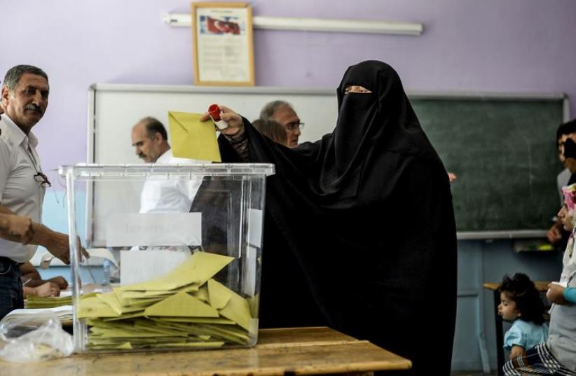 A woman casts her vote as others wait on June 7, 2015, in the southeastern city of Diyarbakir (photo credit: BULENT KILIC / AFP)