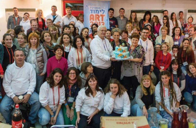 Limmud FSU founder Chaim Chessler, center with cake, together with secretarygeneral Diane Wohl and participants at Limmud FSU Art Jerusalem in 2012. (photo credit: LIMMUD)