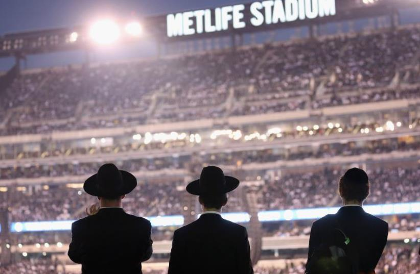 Orthodox Jews gather to celebrate the completion of study of the entire Talmud religious text in East Rutherford, New Jersey (photo credit: AFP PHOTO)