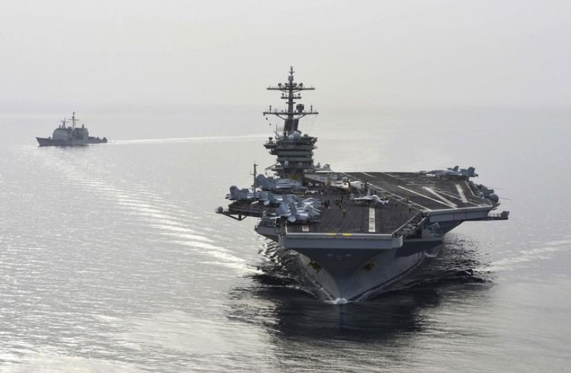 The aircraft carrier USS Theodore Roosevelt (CVN 71) and the guided-missile cruiser USS Normandy (CG) 60 sail in the Arabian Sea, in this US Navy photo taken April 16, 2015 (photo credit: REUTERS)