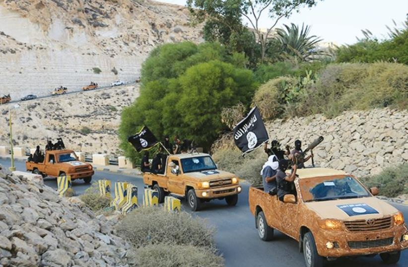 An armed motorcade belonging to members of Derna's Islamic Youth Council drives along a road in the town of Derna in eastern Libya on October 3, 2014, a day after the group pledged allegiance to the Islamic State. (photo credit: REUTERS)