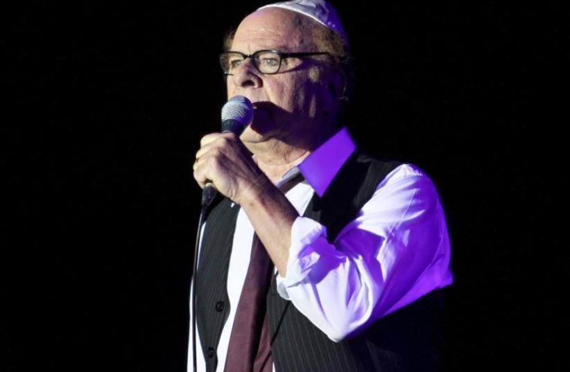 Art Garfunkel performs on stage at the Bloomfield Stadium in Tel Aviv, on June 10, 2015. (photo credit: GIL COHEN MAGEN / AFP)