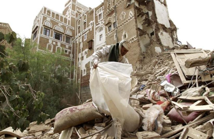 A worker searches through the rubble after Saudi-led strikes targeted the old city of Sanaa, Yemen (photo credit: MOHAMMED HUWAIS/ AFP PHOTO)