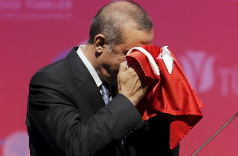 Turkey's President Recep Tayyip Erdogan kisses a handmade Turkish flag in Ankara (photo credit: REUTERS)