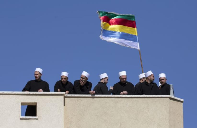 Members of the Druze community stand near a Druze flag during a rally in the Druze village of Majdal Shams. (photo credit: REUTERS)