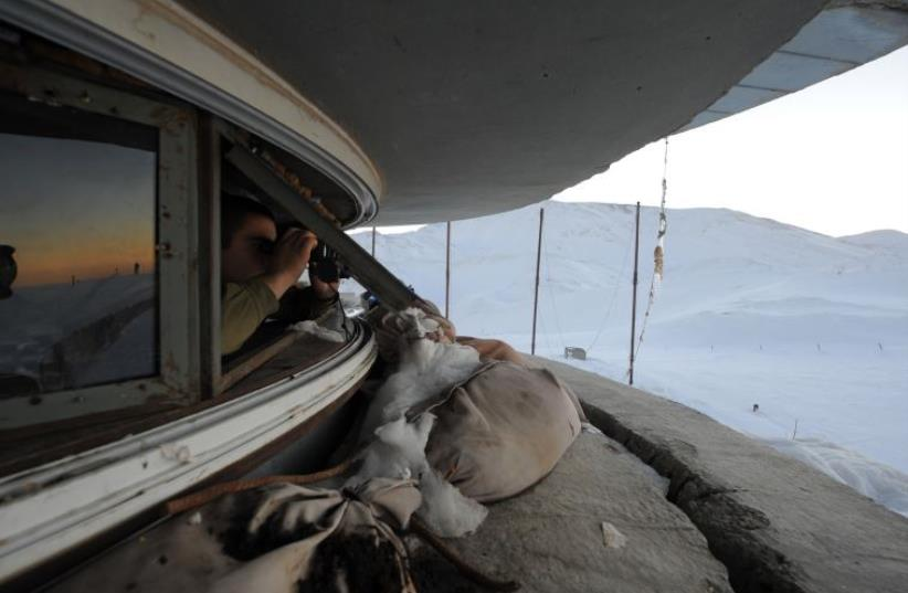 An IDF soldier looks out from a position on Mt. Hermon (photo credit: IDF SPOKESPERSON'S UNIT)
