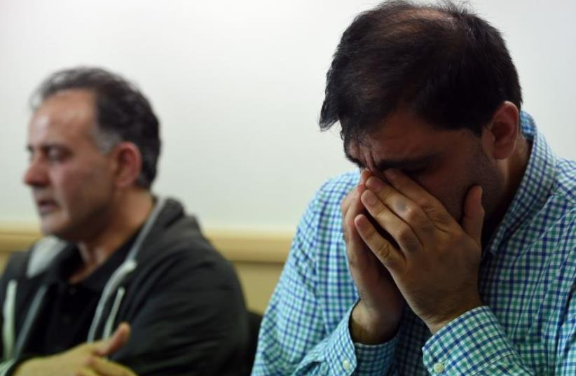 Akhtar Iqbal, husband of Sugra Dawood (L), and Mohammed Shoaib, husband of Khadija Dawood, react during a news conference to appeal for the return of their wives and children, in Bradford, northern England (photo credit: PAUL ELLIS / AFP)