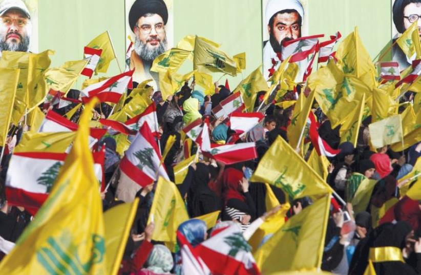 LOCALS IN NABATIYA, south Lebanon, carry Hezbollah and Lebanese flags on May 24 while the group's leader Hassan Nasrallah speaks on a screen at a festival to commemorate the 15th anniversary of the IDF's withdrawal from Lebanon (photo credit: REUTERS)