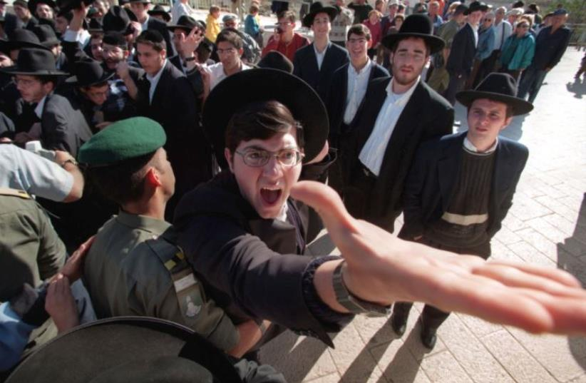 An ultra-orthodox Hassidic Jew is restrained by a Border Policeman as he screams against a group of Reform and Conservative rabbis holding prayers at the Western Wall (photo credit: REUTERS)