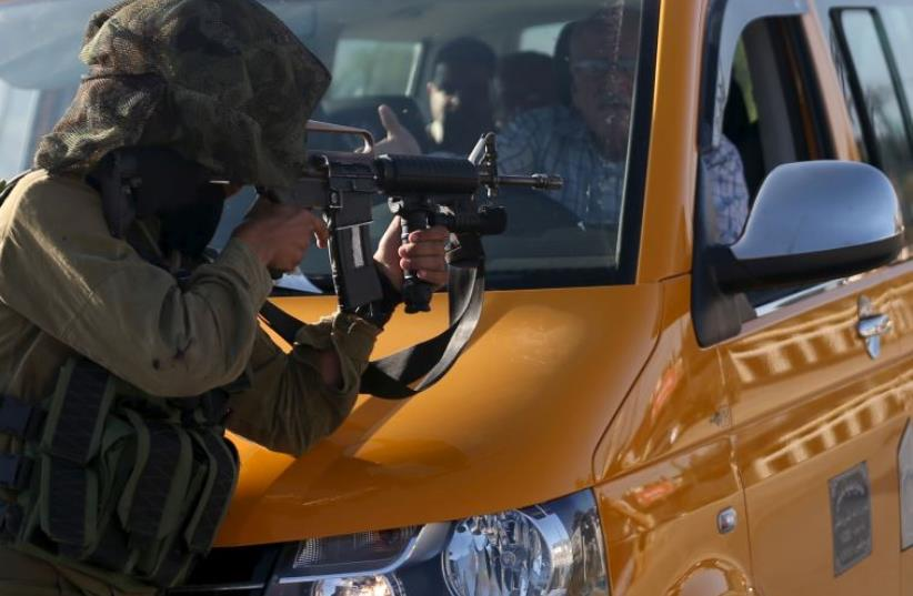 A driver stops his vehicle in front of an IDF soldier who is aiming his weapon at demonstrators during clashes with Palestinians in Jalazoun refugee camp (photo credit: REUTERS)