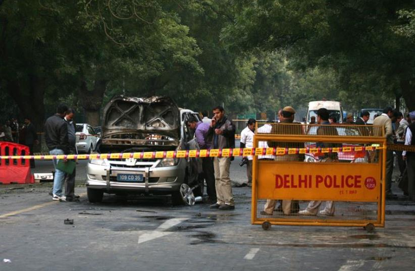 Police and forensic officials examine a damaged Israeli embassy car after an explosion in New Delhi February 13, 2012. (photo credit: REUTERS)