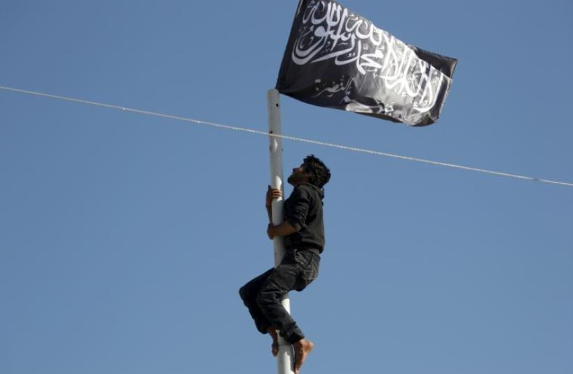 A member of al-Qaida's Nusra Front climbs a pole where a Nusra flag was raised at a central square in the northwestern city of Ariha (photo credit: REUTERS)