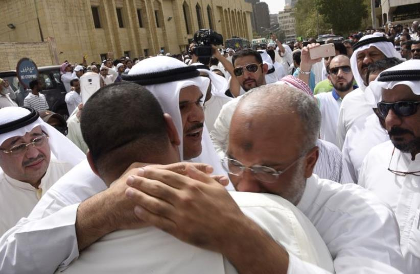Kuwaiti Information Minister Sheikh Salman al-Humoud al-Sabah (C) consoles worshipers outside the Imam Sadiq Mosque after a suicide bomb attack following Friday prayers (photo credit: REUTERS)