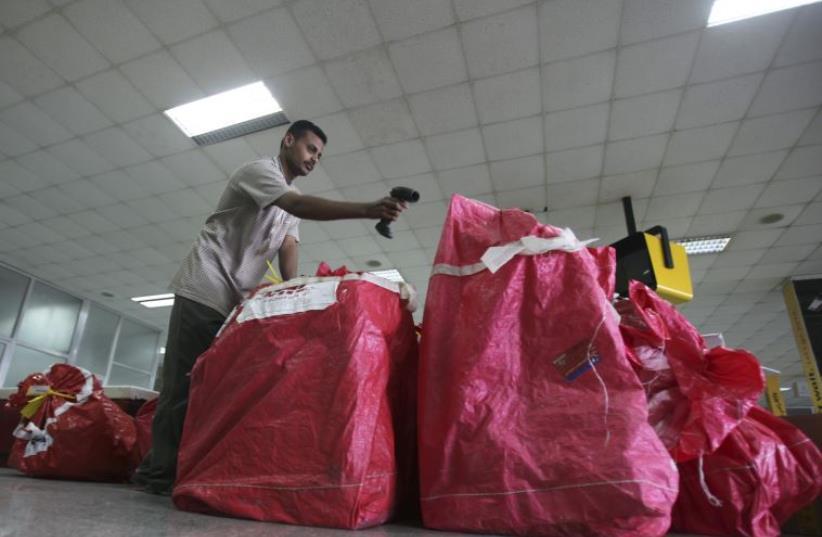 A DHL worker checks parcels at Sanaa International Airport. (photo credit: REUTERS)