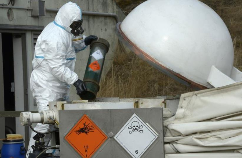 A worker dressed in protective clothing, handles a dummy chemical World War Two weapon. (photo credit: REUTERS)