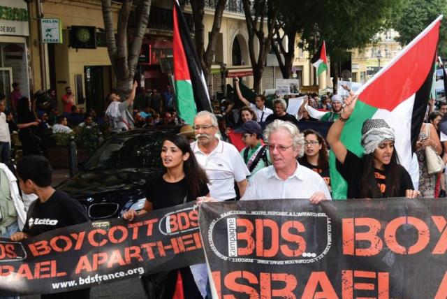 Anti-Israel demonstrators march behind a banner of the BDS organization in Marseille, June 13. (photo credit: GEORGES ROBERT / AFP)