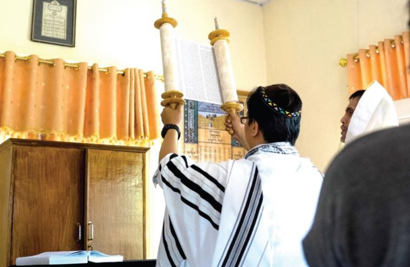 Vicktor (Noah) Ratumbanua holds the Torah during Saturday morning services. (photo credit: ANNA CLARE SPELMAN)