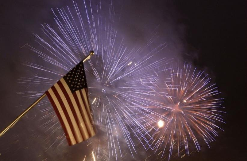 Fireworks illuminate the sky next to a US flag (photo credit: REUTERS)