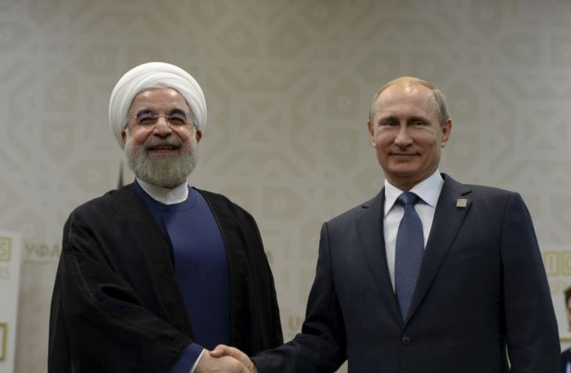 Russian President Vladimir Putin shakes hands with Iran's President Hassan Rouhani during their meeting in Ufa, Russia, July 9, 2015. (photo credit: REUTERS)