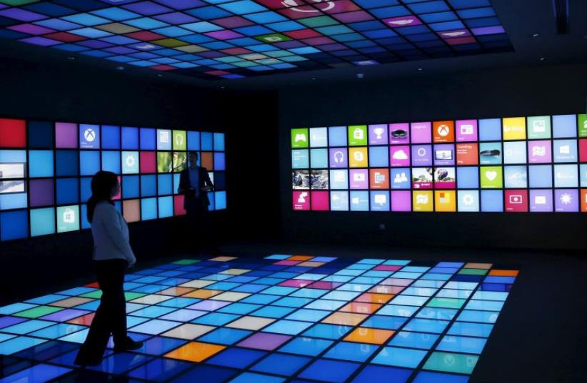 A reporter looks around a display of Microsoft China Center One (photo credit: REUTERS)